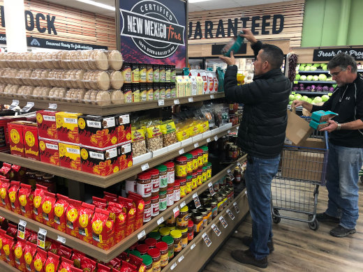 man stocking grocery shelves